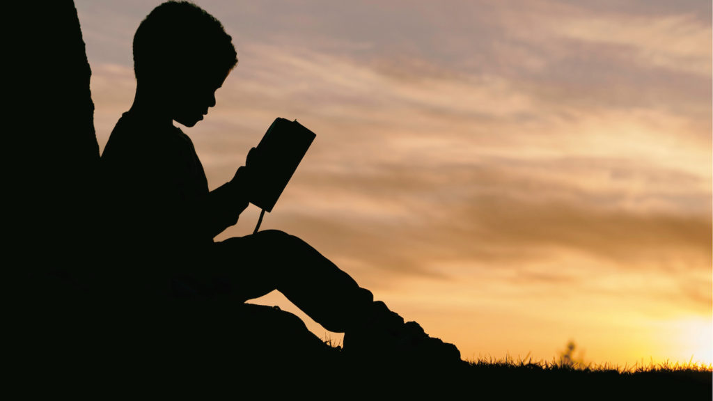 夕暮れに本を読む少年